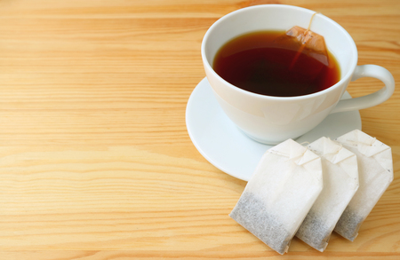 Tea bags and a cup of freshly brewed hot tea with tea bag served on wooden table