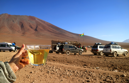 Females hand holding a cup of morning tea at the Chile-Bolivia border with many off road vans for Bolivia Altiplano adventure Banco de Imagens