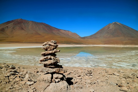 Stone Stack Made by Traveler on the Shore of Laguna Verde or Green Lake with Lincancabur Volcano in the backdrop, Potosi, Bolivia Imagens