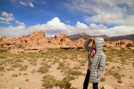One Female Tourist Looking at the Amazing Landscape with Plenty of Rock Formations in Siloli Desert, High Altitude Expanse of Potosi, Bolivia