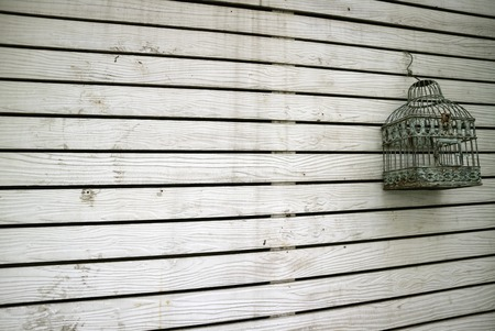 Diminishing perspective of white colored old wooden plank wall with an empty bird cage