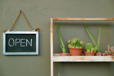 OPEN sign board hanging on the cafe outer wall beside the succulent plants shelf