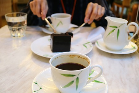 Half cup of black coffee with blurry hands cutting dark chocolate cake in the backdrop 스톡 콘텐츠