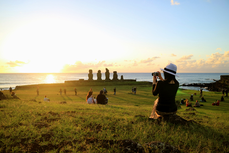 Female Tourist Taking Photos of the Famous Sunset Scene at Ahu Tahai, Archaeological site on Easter Island, Chile 版權商用圖片