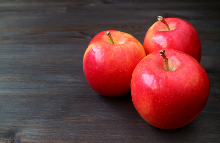 Three red apples on dark colored wooden table with free space for text and design