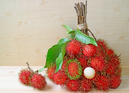 Bunch of Bright Color Red and Green Fresh Ripe Rambutan Whole Fruits and Peeled Isolated on Wooden Table