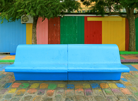 Vivid Blue Concrete Bench in front of Colorful Wooden Wall at La Boca Neighborhood of Buenos Aires, Argentina