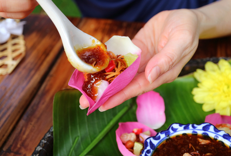 Hand Putting Sweet and Spicy Dip into Thai Style Fresh Lotus Petal Wrapped Appetizer Holding in Hand Stock Photo