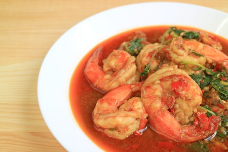 Plate of Thai Style Spicy Stir Fried Prawns with Holy Basil Served on Wooden Table