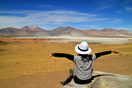 Woman Raising Her Arms In Front of Awesome View of Salar de Talar salt Lakes and Cerro Medano Mountain, Chilean Andes, Northern Chile