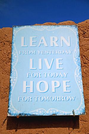 Lavagna per citazioni ispiratrici di colore azzurro sul muro di argilla Archivio Fotografico