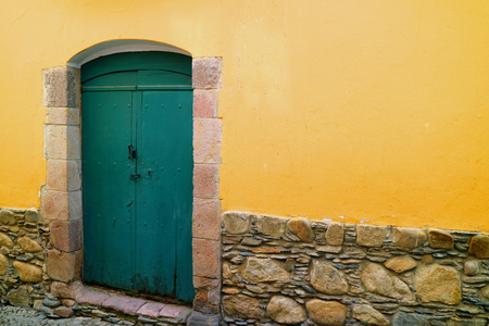Green wooden door on the yellow wall of an old colonial building on Jaen street, La Paz, Bolivia Archivio Fotografico