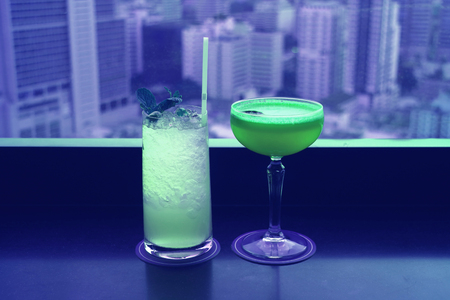 Two different type of cocktails in vibrant green color on the rooftop bars table with blurry skyscrapers view in background Stok Fotoğraf