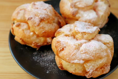 Closeup French Cream Puffs on Black Plate Sprinkled with Icing Sugar
