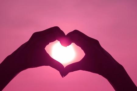 Roze gekleurd silhouet van de hand van de vrouw die het teken van het LIEFDE HART tegen de glanzende zon stelt