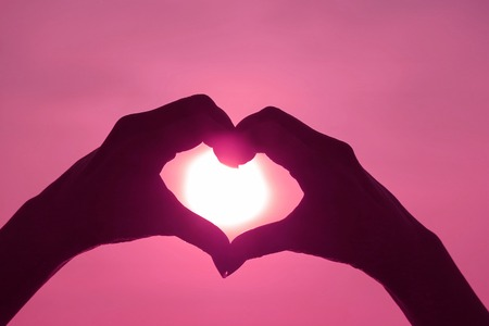 Silueta de color rosa de la mano de la mujer posando signo de corazón de amor contra el sol brillante