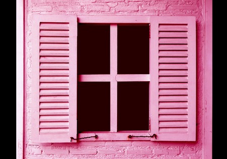 Pink colored window shutters on the pink brick wall
