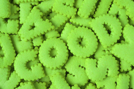 Heap of bright green alphabet shaped biscuits spelling the word GOOD