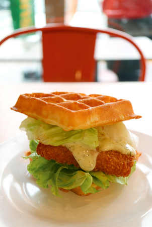 Vertical image of fish fillet waffle sandwich with fresh lettuce