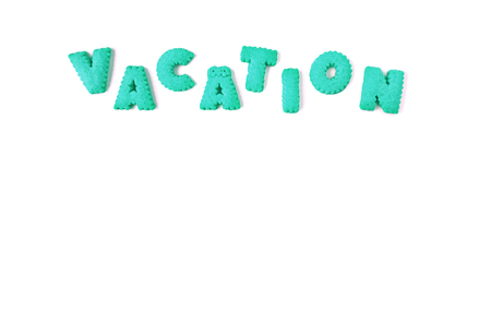 The word VACATION spelled with vibrant aqua blue color alphabet shaped cookies on white background