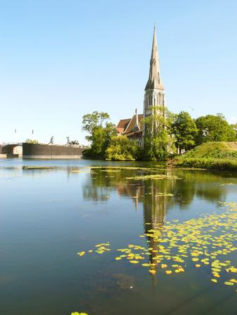 Vertical image of Saint Albans church on the lakeside of the Kastellet fortress in Copenhagen, Denmark, Europe