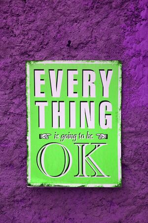 Pop art style neon green signboard of EVERYTHING is going to be OK on the rough vivid purple wall