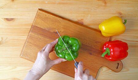 Womans hand cutting a green bell pepper on wooden cutting board