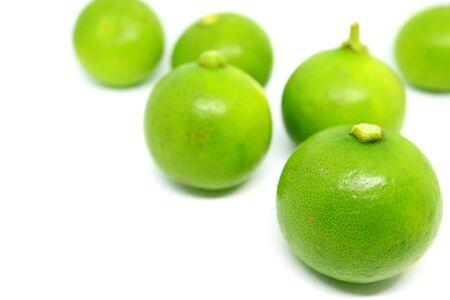 Closeup vibrant green limes isolated on white background
