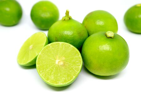 Fresh lime in cross sections with whole fruits scattered on white background
