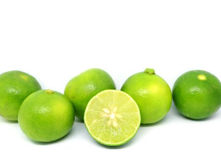 Cut fresh lime with whole fruits rowed up on white background