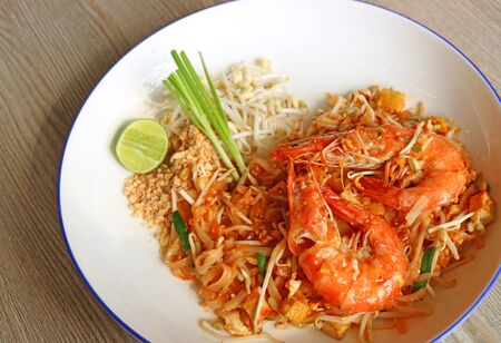 Thai Style Fried Noodle or Pad Thai Topped with Prawns Served on Wooden Table