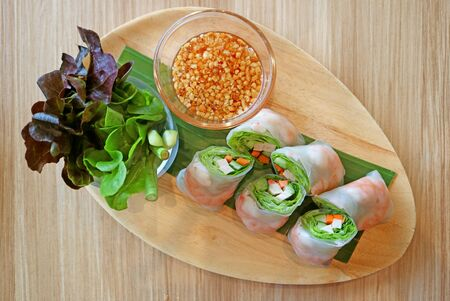 Prawn and fresh vegetable spring rolls served with green salad on a wooden plate
