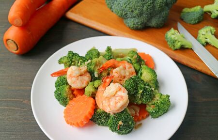 Plate of prawn stir fried with broccoli and carrot with blurry cut vegetables in background