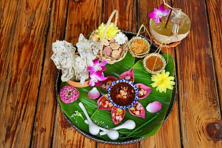Thai Appetizer Set of Fresh Lotus Petal Wrapped and Crispy Fried Rice Cakes with Calamansi Citrus Juice Served on Wooden Table Stock Photo