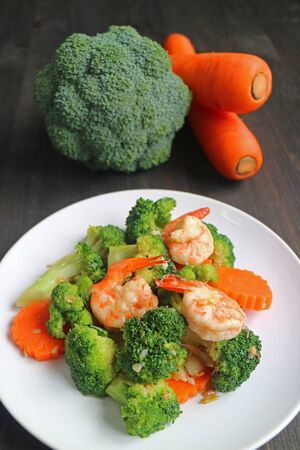Healthy dish of prawn stir fried with broccoli and carrot served on white plate Stock Photo