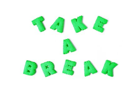 The word TAKE IT EASY spelled with lime green color alphabet shaped biscuits on white background