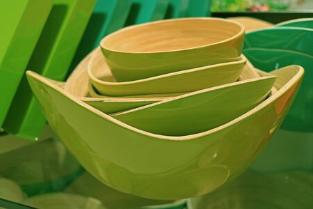 Stack of vibrant green wooden bowls in different sizes
