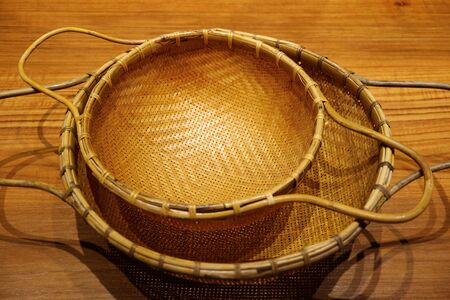 Vintage style woven bamboo colanders isolated on wooden table