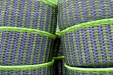 Stack of vibrant green and purple colored wicker baskets