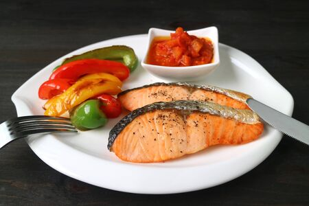 Healthy dish of grilled salmon steaks with colorful vegetables served on dark brown wooden table