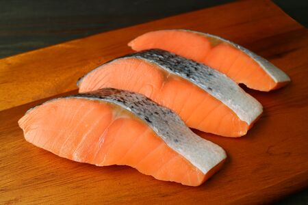 Three pieces of sliced fresh raw salmons on a wooden cutting board Stock Photo