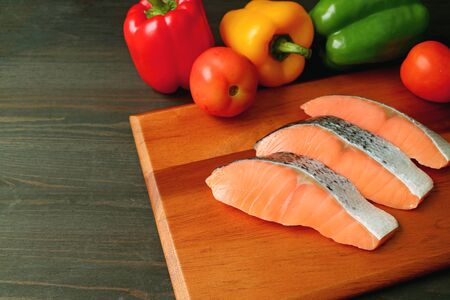 Uncooked raw sliced salmon on a wooden cutting board with fresh colorful vegetables