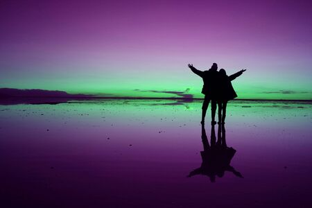 Pop art styled silhouette of couple raising arms for the happy moment on Uyuni Salt Flats, Bolivia, South America Stock Photo
