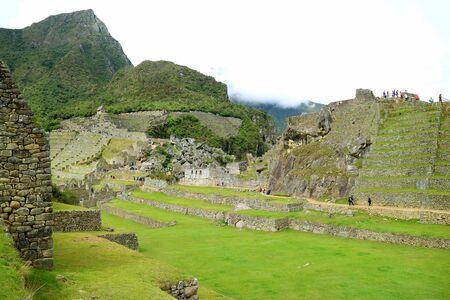 Visitors Enjoy Exploring inside the Remains of Machu Picchu Inca Citadel, Cusco, Peru, South America Stock Photo