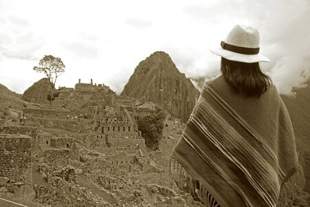 Sepia Image of Female in Poncho Looking at the Amazing Inca Ruins of Machu Picchu, Cusco Region, Peru, South America