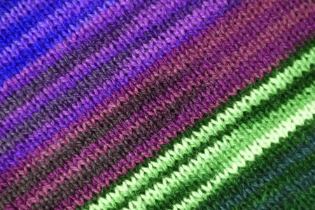 Texture of the Diagonal Stripe Patterns of Purple and Green Color Toned Alpaca Knitted Wool Fabric