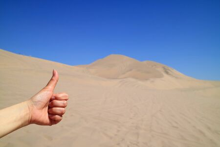 Womans Hand Thumbing Up to the Amazing View of Huacachina desert in Ica region of Peru, South America Stock Photo