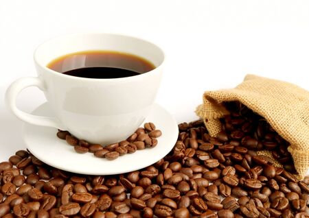Cup of hot coffee with roasted coffee beans scattered from burlap bag on white background Stock Photo