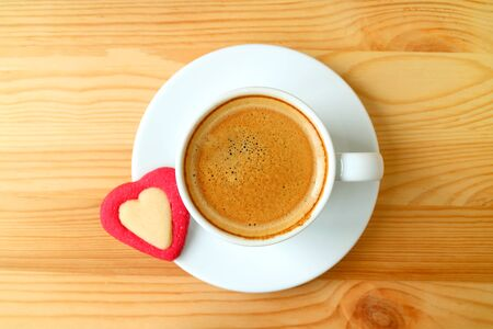 Top view of an espresso coffee with a heart shaped cookies served on wooden table Stock Photo
