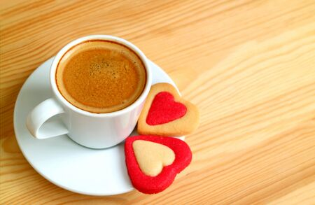 Cup of hot coffee with a pair of heart shaped cookies on wooden table with copy space